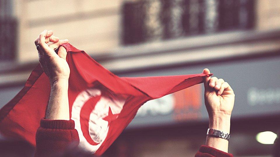 Man holding Tunisian flag