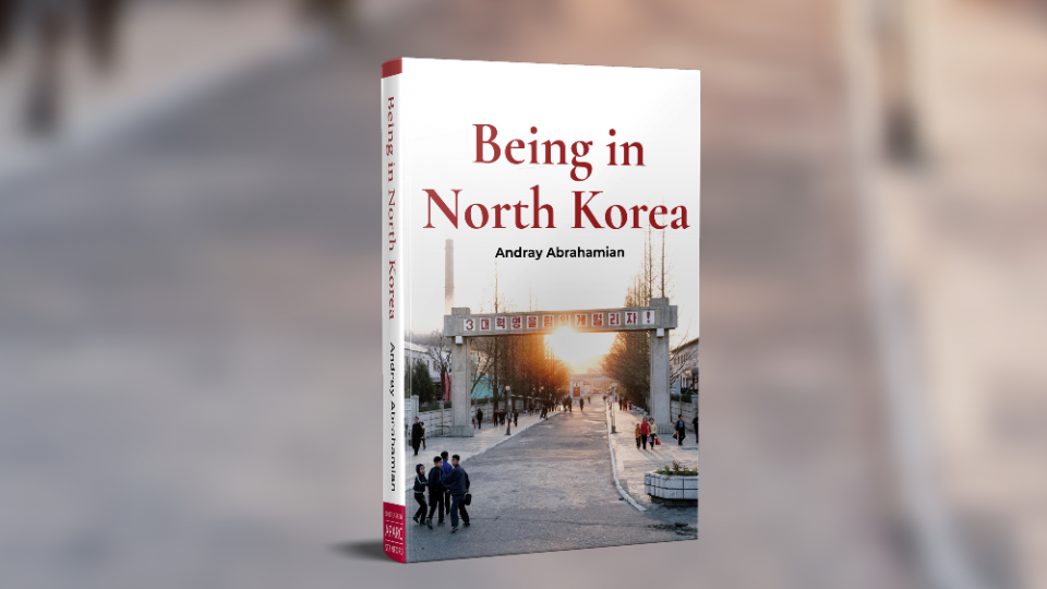 Cover of the book 'Being in North Korea' by Andray Abrahamian on a blurred background of a road, a cropped scene from the cover image