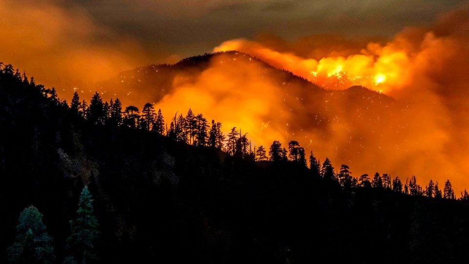 A bright orange wildfire burning on a dark hilside