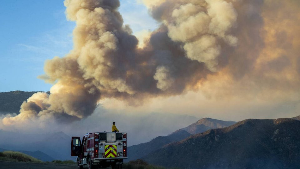 Firefighters in a firetruck looking at a landscape of mountains and a sky filled with smoke