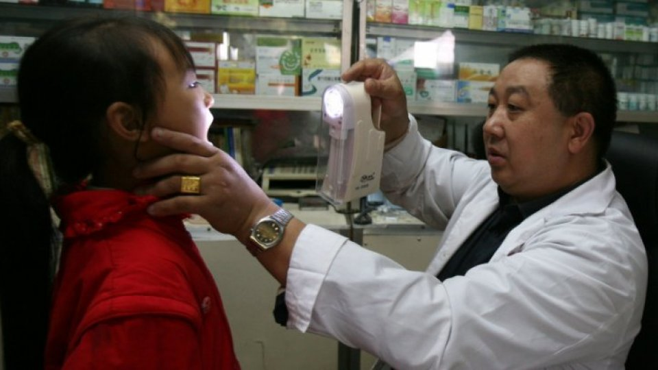 A doctor checks a young girl in a countryside clinic in China