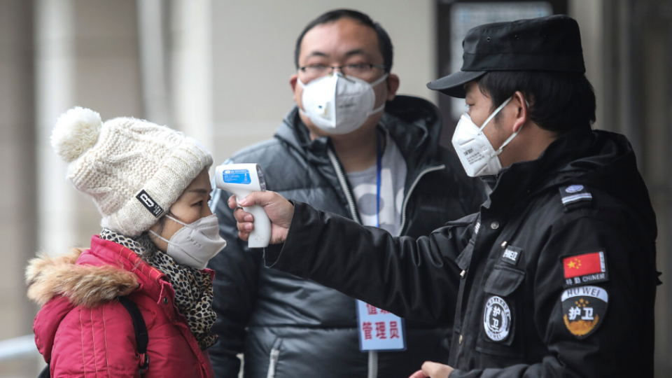 Security personnel check the temperature of passengers in the Wharf at the Yangtze River on January 22, 2020 in Wuhan, Hubei province, China.