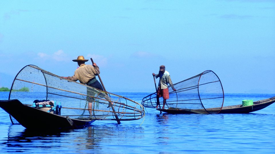 Two fisherman with large nets in the ocean