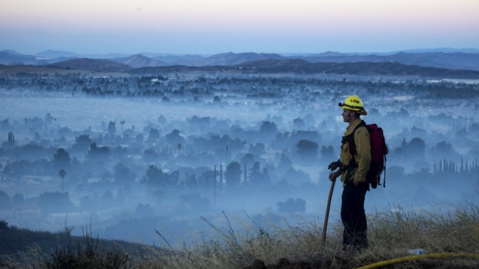 A firefighter standing on a hill overlooking a smokey city during the Apple Fire.