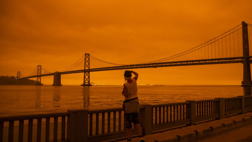 A person looking out at the Bay Bridge in San Francisco under a dark orange sky