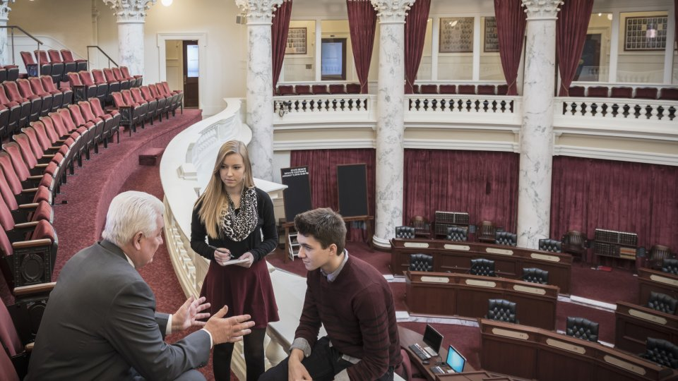 Caucasian teenagers talking to politician in capitol buildin