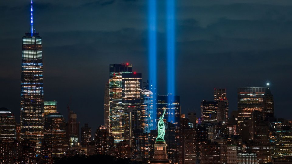 New York City skyline with The Tribute in Light 9/11 memorial and the Statue of Liberty.