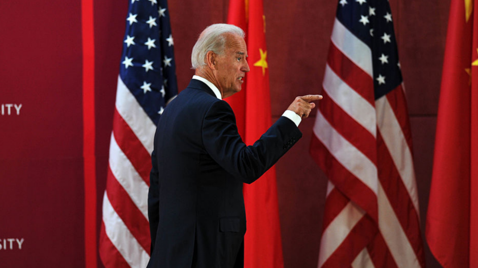 President Biden walks past a row of Chinese and American flags.