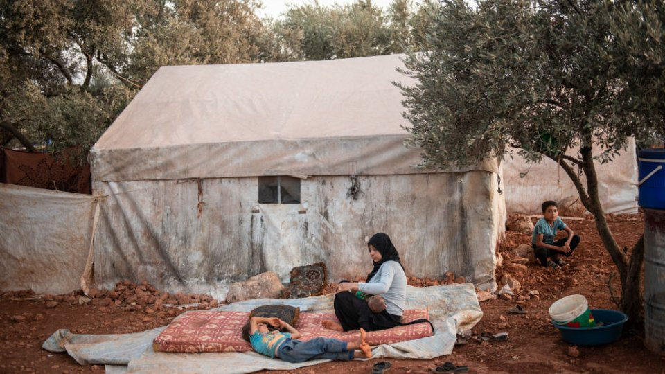 Syrian Refugees sitting in front of tent
