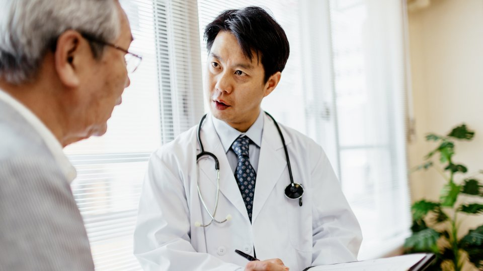 Male Japanese doctor showing senior patient records on a clipboard