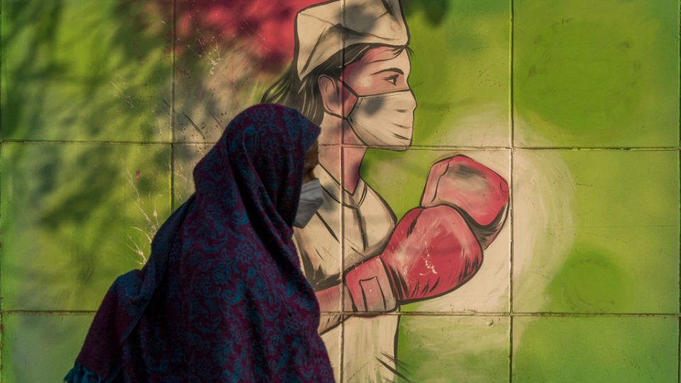 A woman walks past a mural referring to the Covid-19 coronavirus painted on a wall on December 10, 2020 in New Delhi, India.
