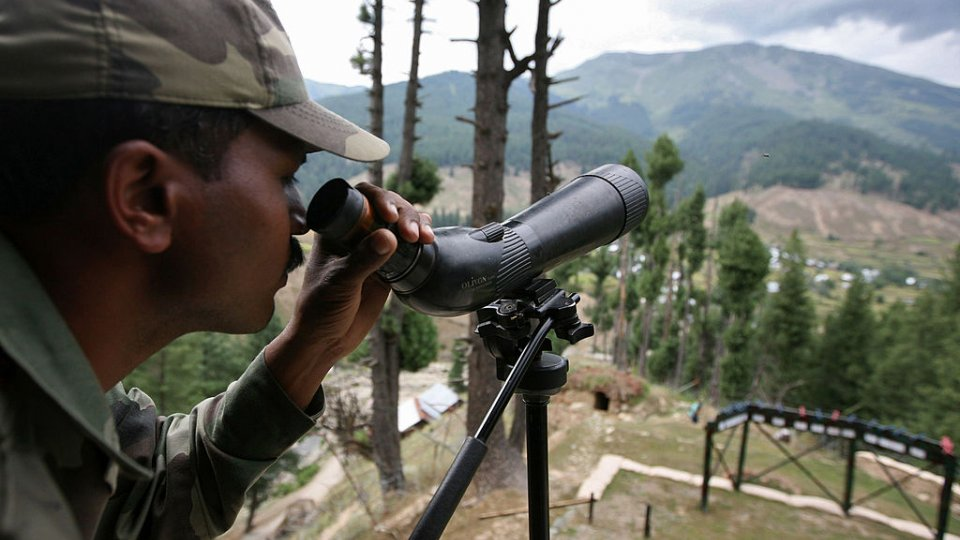 An Indian Army soldier looking through a military monocular over hills in the background