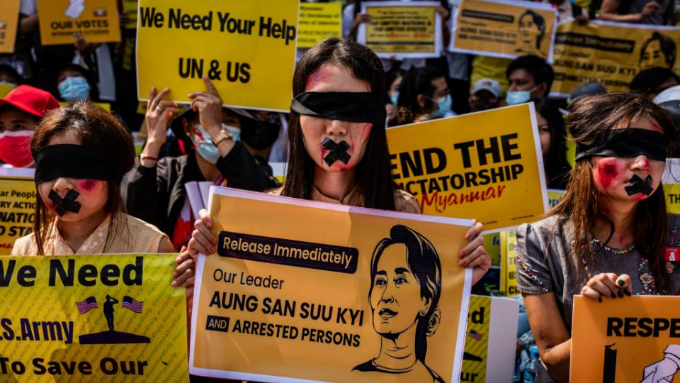 Protesters against the military coup in Myanmar hold banners.