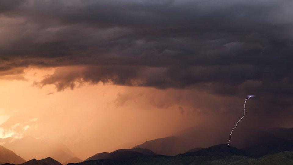 Lightning striking a mountain amidst a dark cloudy sky