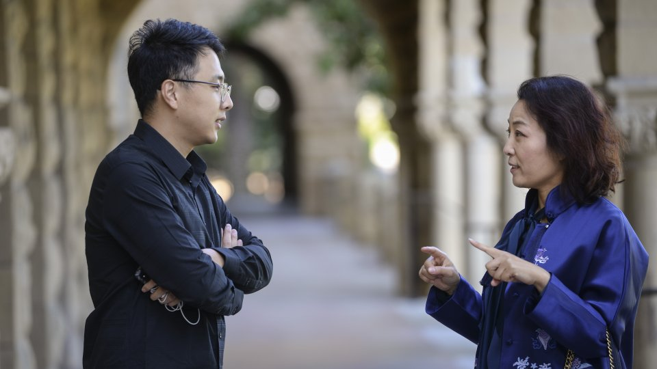 Two young scholars (man and woman) speaking at Encina Hall colonnade
