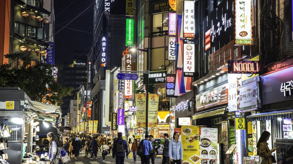 Crowds pass under the Myeongdong neon lights, Seoul, South Korea