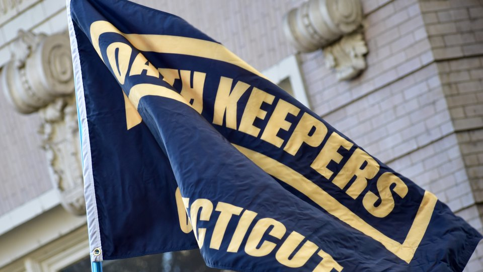 Image displays a black flag with Oath Keepers written on it in yellow text