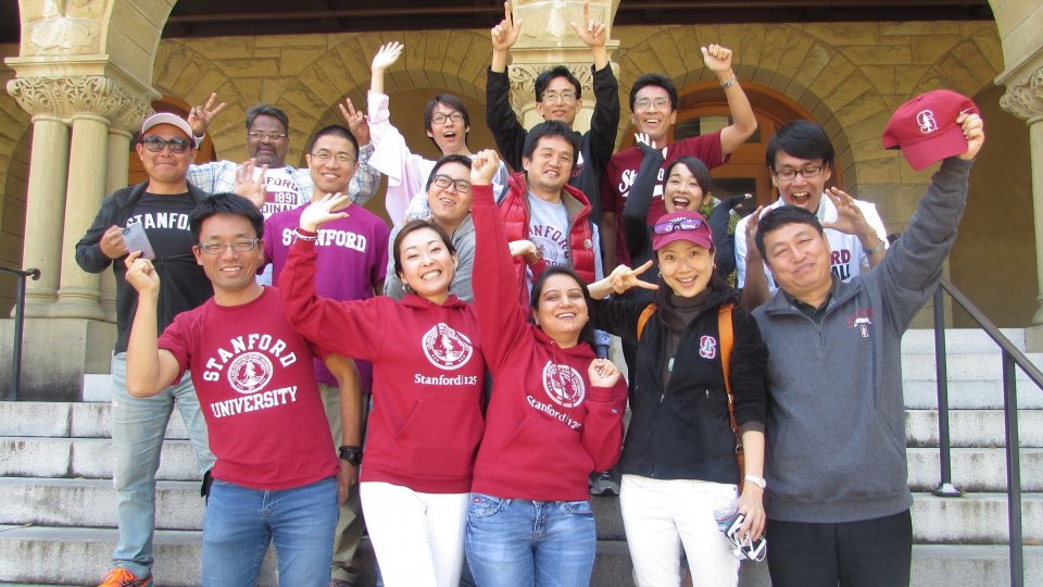 A cohort of visiting scholars with the Global Affiliates Program posing to the camera at the entrance to Encina Hall, Stanford