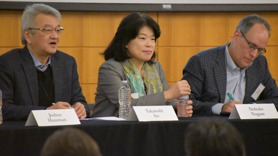 Three panelists, two males and a female, speaking at a Japan Program conference.