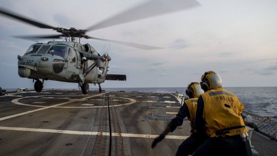 U.S. Navy Boatswain's Mate Seaman Louie Beasley, Jr., from Oklahoma City, directs an MH-60S Sea Hawk, assigned to Helicopter Sea Combat Squadron (HSC) 25, while landing on the flight deck of the guided-missile destroyer USS Preble (DDG 88) during deck lan