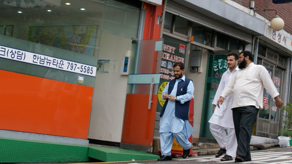 Three men wearing Islamic clothing walk down a street in the Itaewon neighborhood in Seoul, South Korea.