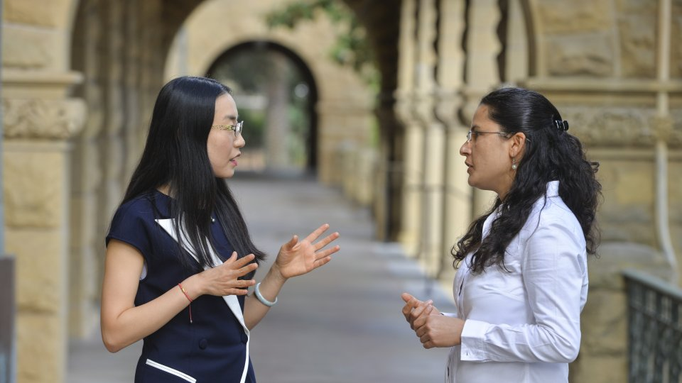 2018-19 postdoctoral scholars Ketian Zhang and Sarita Panday in conversation at the Encina Hall entranceway.