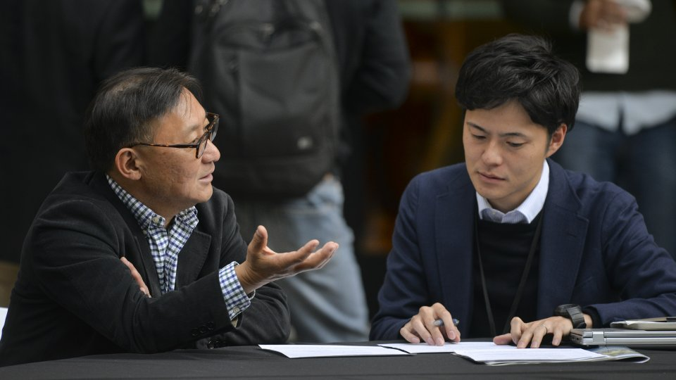 Two men seated in discussion over a paper on the table