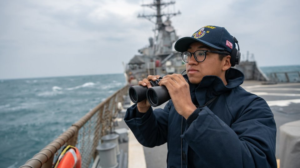 US Pacific Fleet seaman stands lookout on the flight deck as the Arleigh-Burke class guided missile destroyer USS Barry (DDG 52) transits the Taiwan Strait during routine underway operations.