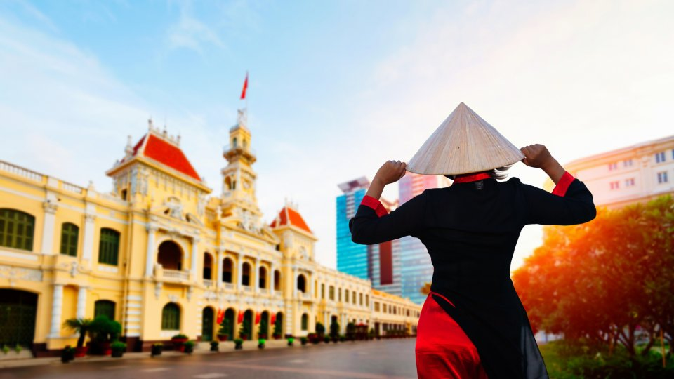 A woman wearing Ao Dai culture traditional at Ho chi minh city hall in Vietnam.