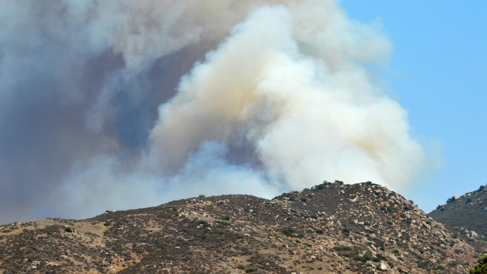 Wildfire smoke rising from behind a dry hill