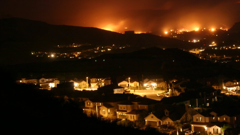 A suburban town at night with wildfires approaching in the distance