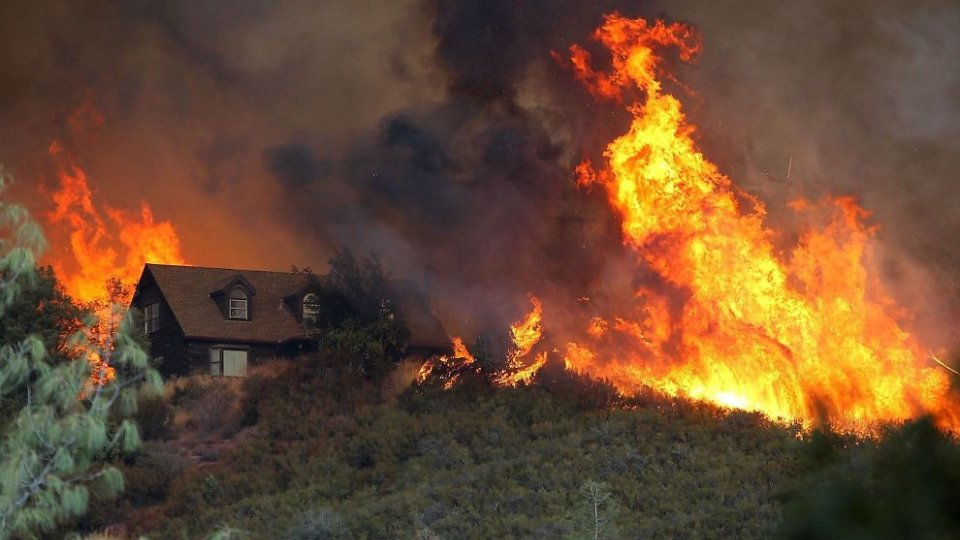 A house on a hill as a large wildfire approaches