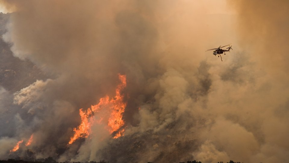 Helicopter flying over large brown plumes of smoke coming from a wildfire
