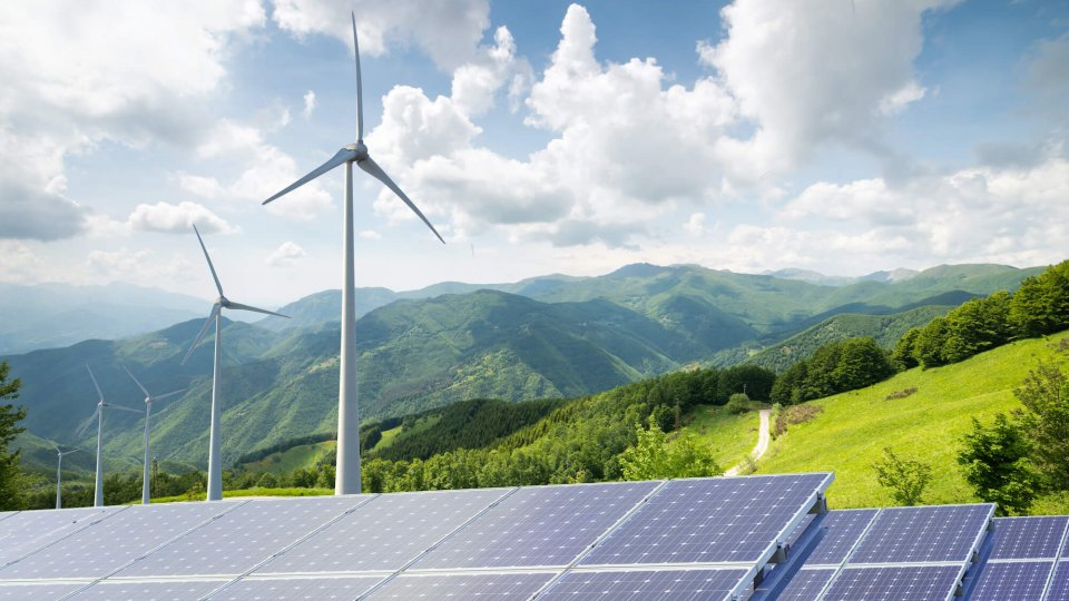 solar panels with wind turbines against mountain landscape against blue sky with clouds