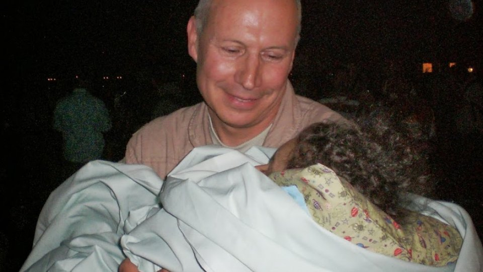 Dean Winslow holds an injured Iraqi child he was able to send to Shriners Burn Center in Boston