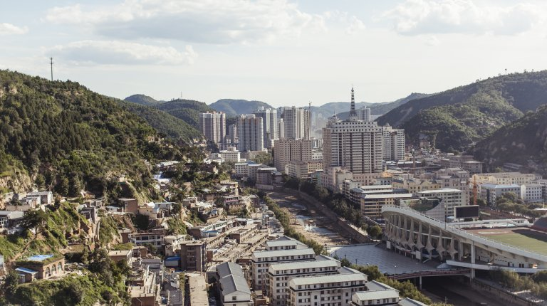 Yulin cityscape showing a green hillside with skyscrapers in the background and a river dividing the industrial city.