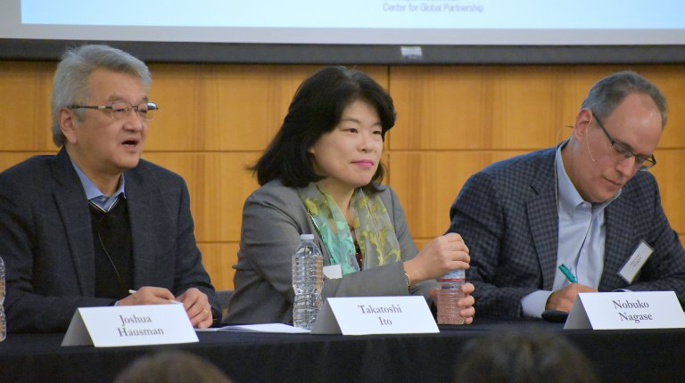 Two men and a woman seated at a table in front of an audience during a panel discussion