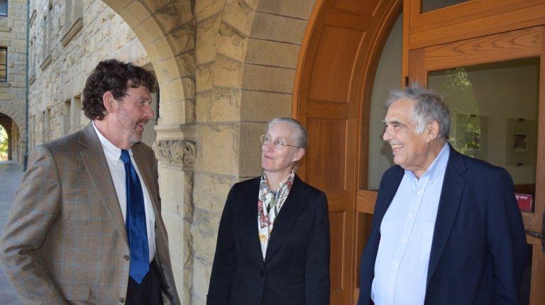 John Donahue, Karen Eggleston, and Richard Zeckhauser in conversation at the entrance to Encina Hall, Stanford.