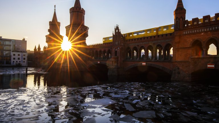 Sunset at the famous Oberbaumbrücke, crossing frozen Spree river (Berlin/ Germany)