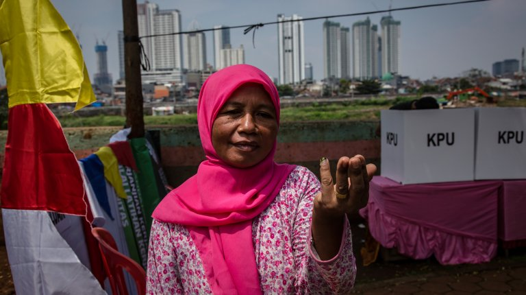 A woman shows her fingers marked with ink after voting at a polling station on April 17, 2019 in Jakarta, Indonesia.