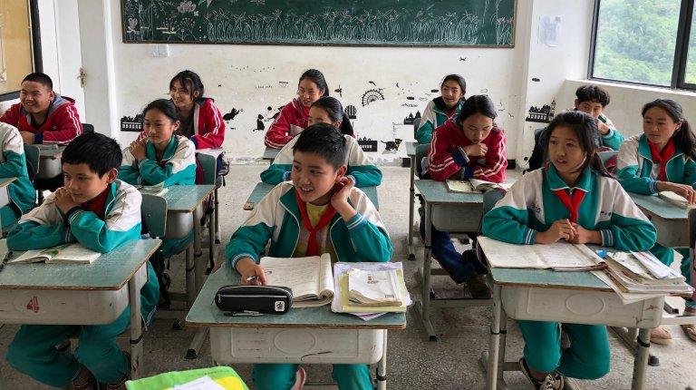 Uniformed kids sitting at desks in a classroom.