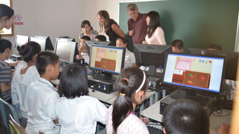 School kids sit in a row working on desktop computers.