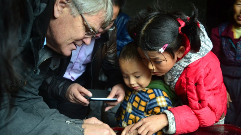Scott Rozelle huddles together with two young children around a table looking at a phone screen and pointing to something on the table.