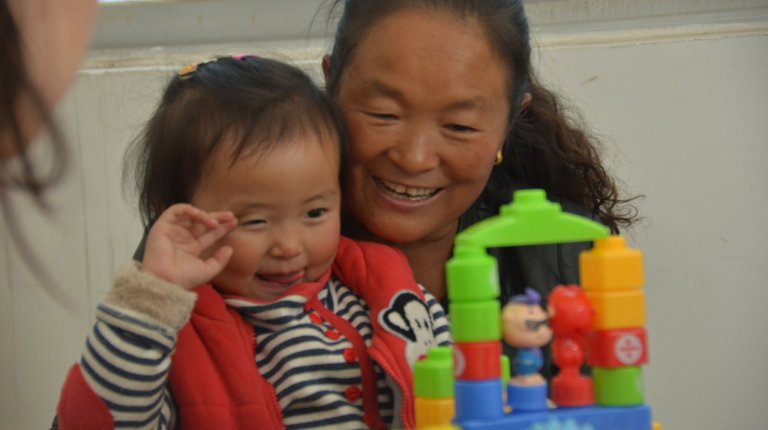 Toddler sitting on mom's lap looking at a colorful plastic building block structure.