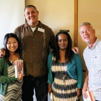 """Professor Adam Johnson poses with happy teachers after signing their new copies of """"The Orphan Master's Son"""" at the 2017 East Asia Summer Institute."""