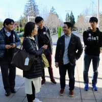 Derek Kenmotsu talks with students and teachers on Apple campus.