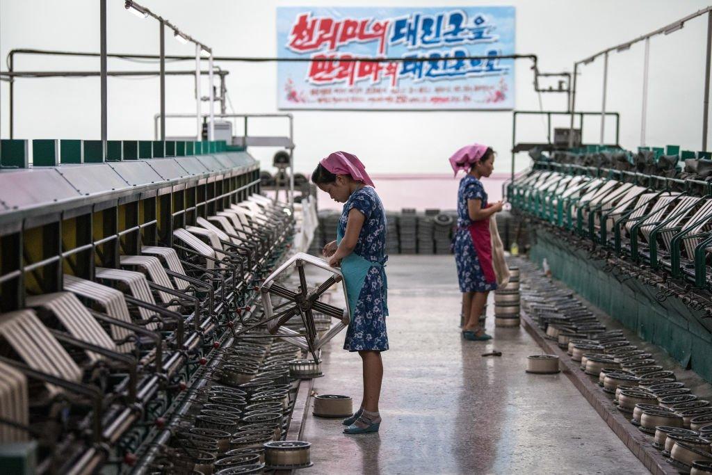 Women work a silk factory beneath a banner with Korean writing.