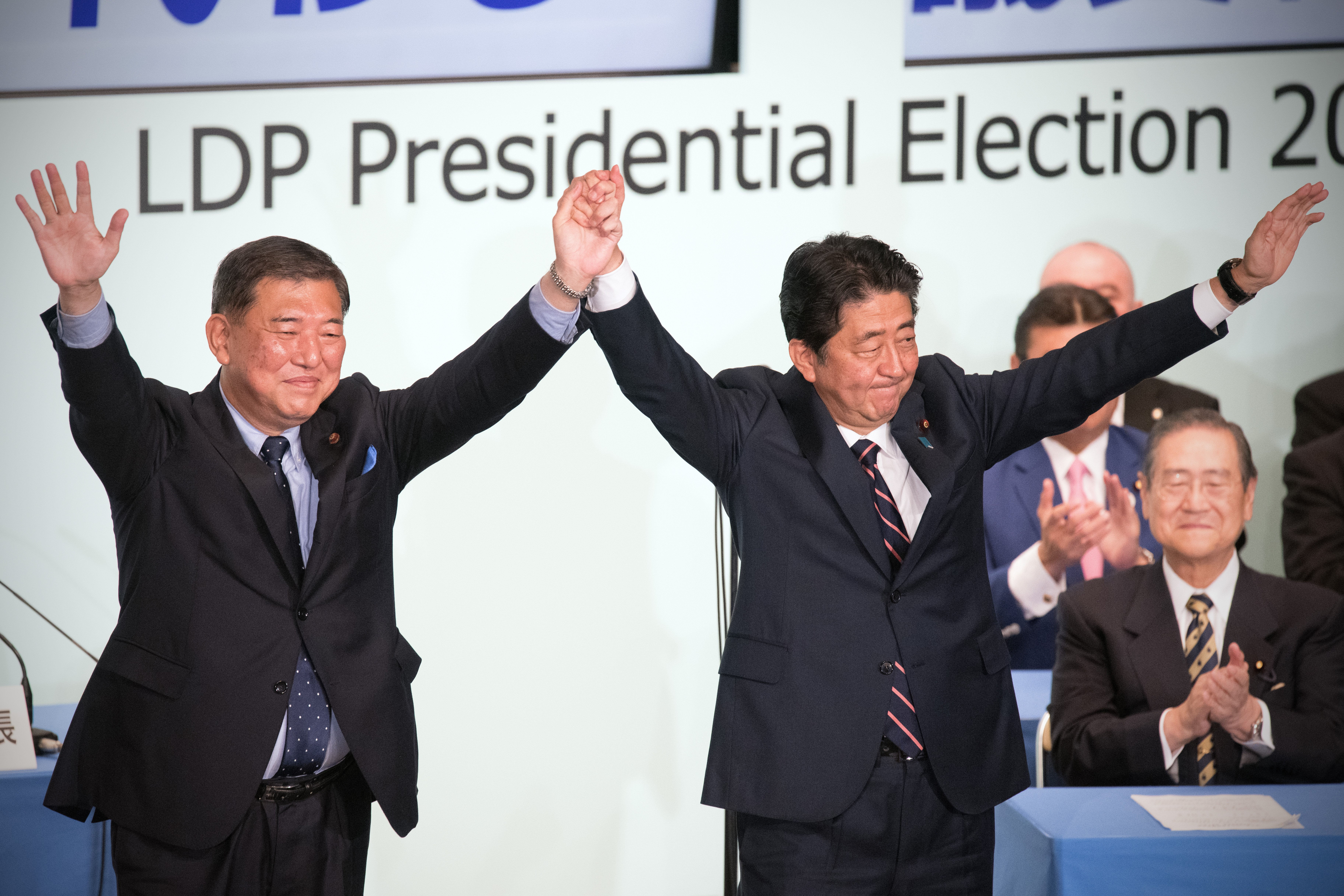 Japan's Prime Minister Shinzo Abe (R) celebrates with Shigeru Ishiba, the former defence minister who ran against him, after winning the Liberal Democratic Party leadership contest on September 20, 2018 in Tokyo, Japan.