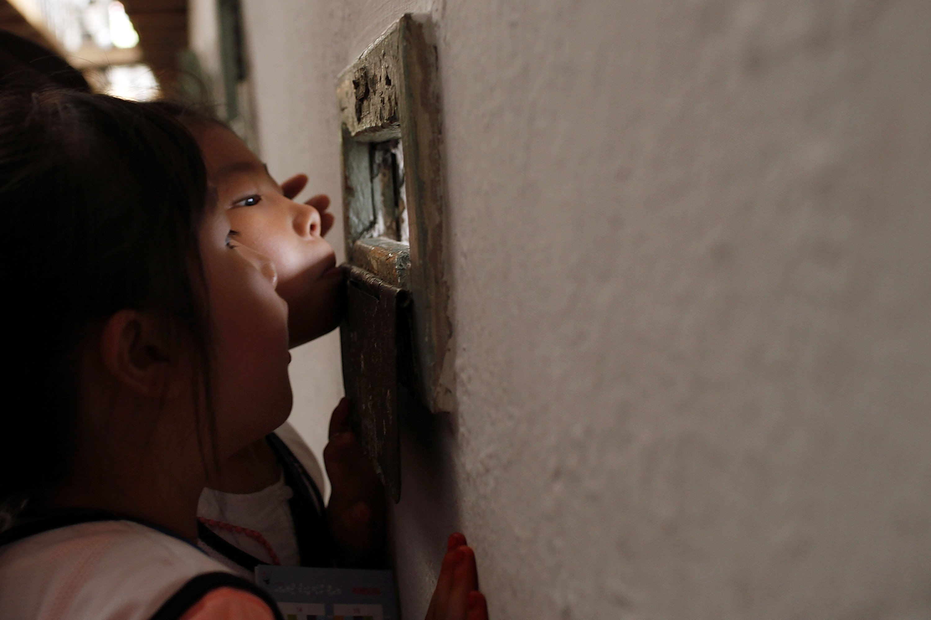 Children look around cells at Seodaemun Prison, the former prison used to lock Independent fighters from 1908, on August 15, 2016 in Seoul, South Korea.