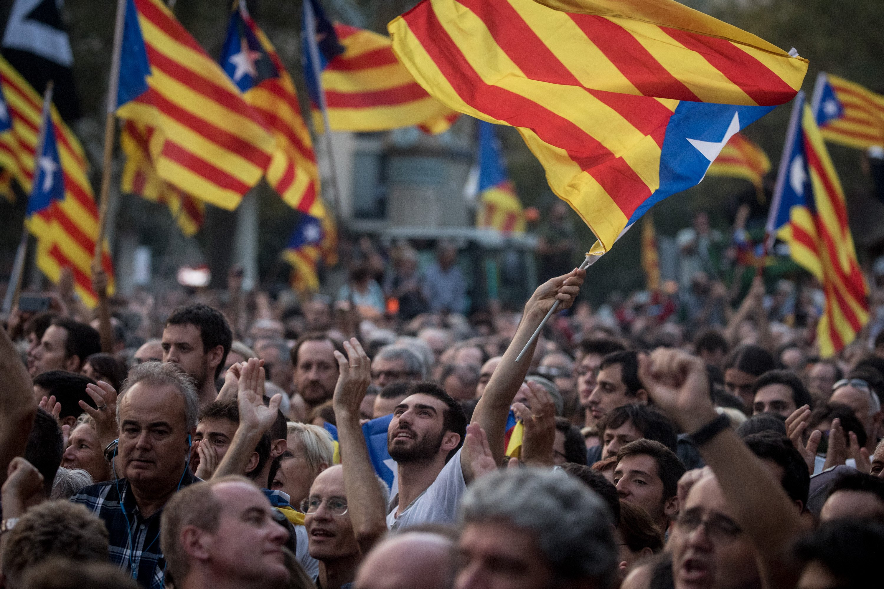 Pro-independence supporters react as they watch a big screen and wait for the address of Catalan President Carles Puigdemont